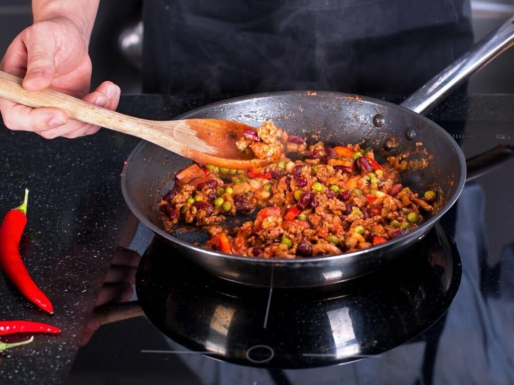 Poêle en inox et chili con carne